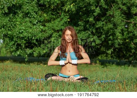 Young woman doing yoga exercise on green park