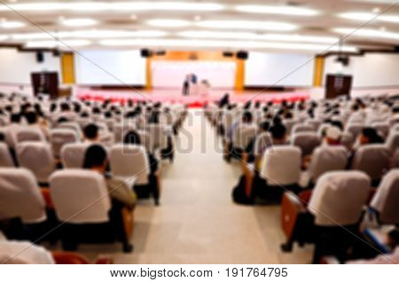 Abstract blurred Asian Speaker talking on stage with Audience or students in the conference hall or seminar meeting business concept education concept