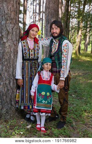 Young family posing in traditional Bulgarian costume during a folklore festival