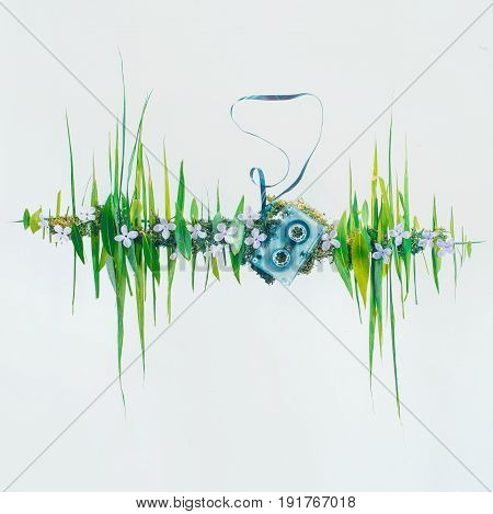 Conceptual photo with sound wave graphic made from leaves and grass. Analogue cassette with music of nature.