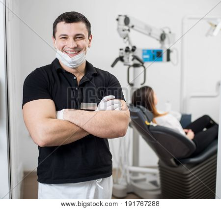 Friendly Male Dentist With Ceramic Brackets Standing With His Hands Crossed At Dental Clinic. On The