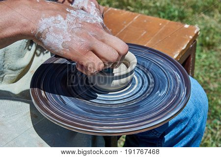 On the potter's wheel revolve a spinning of a clay cup. The potter hands forms a cup