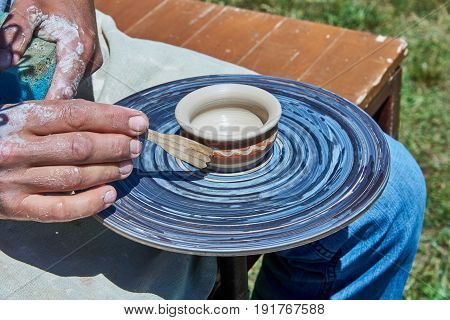 On the potter's wheel revolve a spinning of a clay cup. The potter with a wooden stick forms a picture on the cup