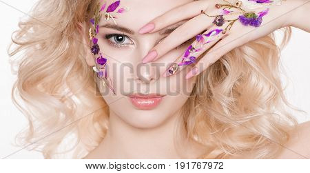 Cosmetics and manicure. Close-up portrait of attractive woman with dry flowers on her face, pastel color of nail design, perfect make-up and skin. Trendy. Studio