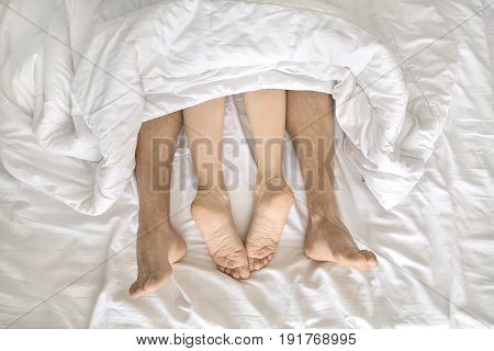 Couple under the white blanket on the bed. Their barefoot legs are sticking out the blanket. Indoors. Closeup. Horizontal.