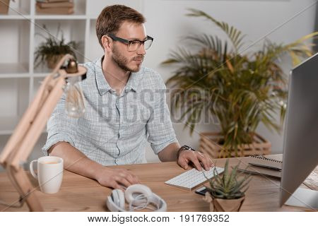 Focused Caucasian Businessman Working With Computer While Sitting At Workspace