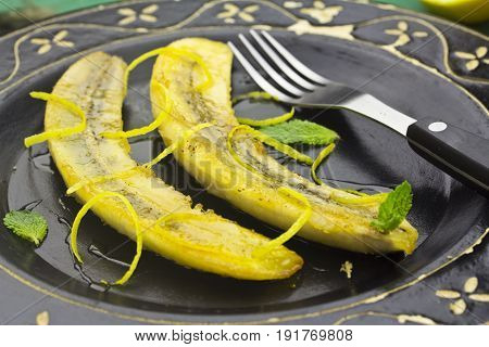 Caramelised bananas with honey and mint on black plate