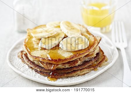 Banana pancakes with maple syrup and orange juice