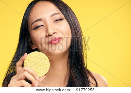 Beautiful, facial, young woman with a sponge, cleans the face of the sponge on a yellow background.