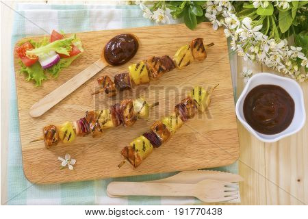 Barbecue pork apple and onion skewer kebabs with side salad