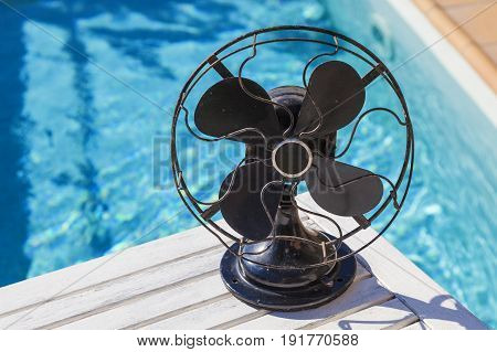 A rusty vintage fan on a hot summer day at the pool