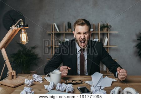 Angry Young Businessman In Suit Yelling While Sitting At Messy Workplace