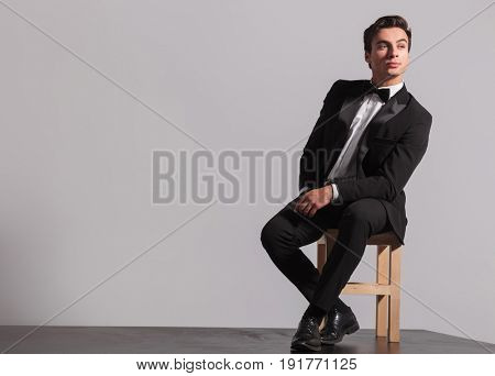 young model in tuxedo and bowtie sits on chair and looks away from the camera on grey background