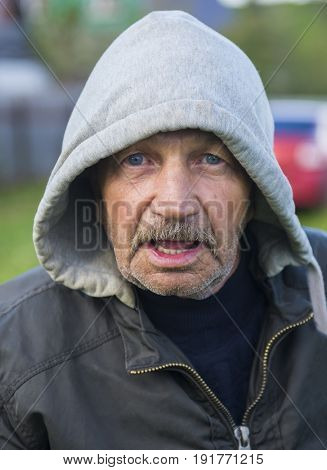 Surprised old man in a jacket with a hood