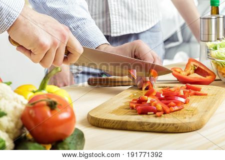 Hands of a man chopped red bell pepper for salad on a board. Couple chopping vegetables in the kitchen
