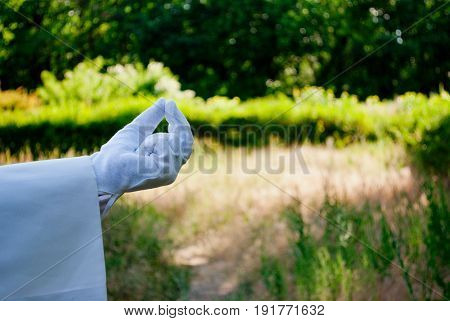 The waiter's hand in a white glove and with a white napkin shows with the fingers a pinch pinch three fingers on the left on a green background of trees and bushes on a blurred background