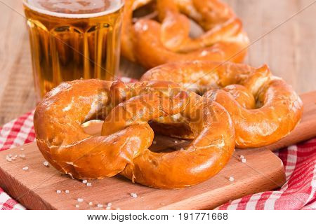 Bavarian pretzels with beer on cutting board.