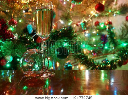Glasses of wine and spirits on the table and a festive sparkling Christmas tree
