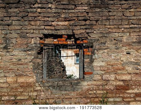 Brick wall of the old destroyed house with textured bricks with an opening in which you can see the window of a residential village house
