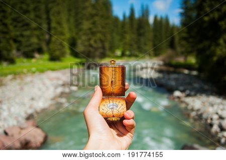 Compass in hands on background a mountain river