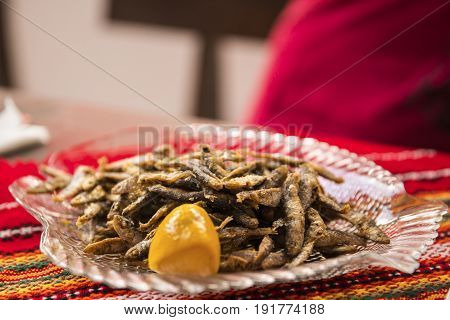 A plate of anchovy fried on a table