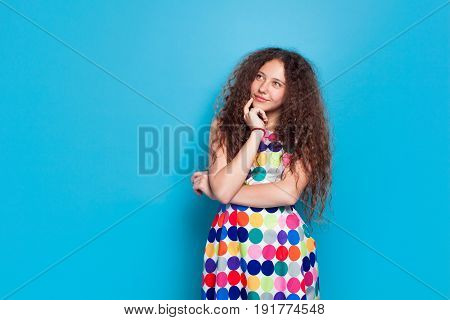 Young girl in bright dress looking pensive on blue background.