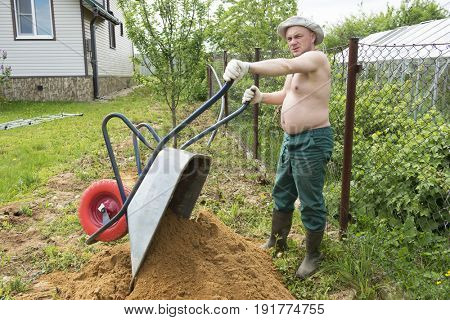 A man loads the sand in a wheelbarrow