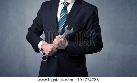 Young, handsome, cute businessman holding tool with grey background