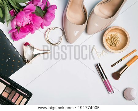 Stylish feminine accessories and pink peonies on white background