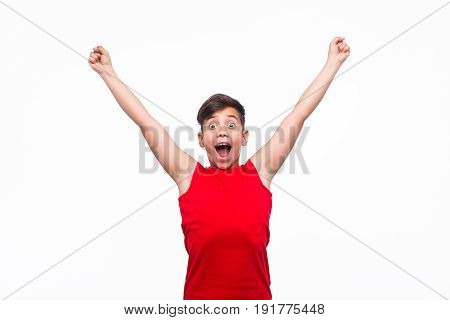 Kid in red tank top holding hands up in gesture of victory and looking at camera.