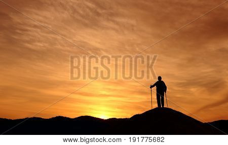 Male mountain climber standing on top of the hill