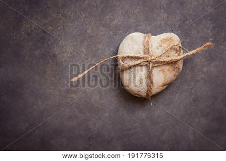 Heart shaped rock pebble tied with twine on dark blue purple stone background conceptual relationship valentine marriage divorce abstract copy space