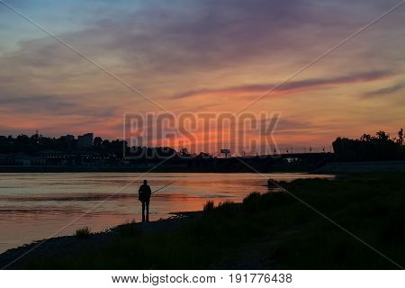 Man fishing at the bank of Angara river after sunset in Irkutsk city