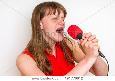 Young woman singing with red microphone - party and celebration concept