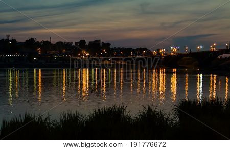 Irkutsk cityscape with Angara river after sunset with bridge and reflection of lights