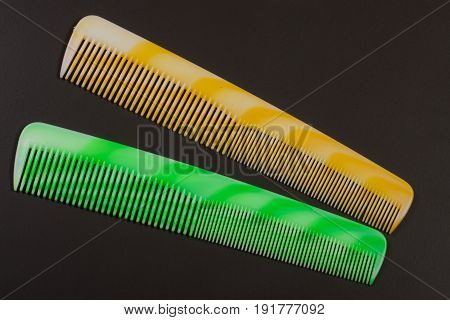 Two different colored hairbrushes on a dark background.