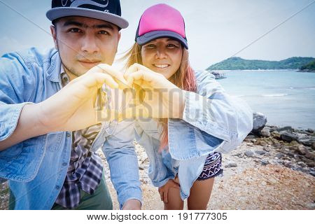 A couple hands in shape of love. Happy smiling young hipster lovers in love sign gesturing heart with fingers form. summer beach casual lifestyle romantic relationship affection happy weekend concept. retro vintage tone.