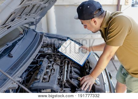 Mechanic technician man holding clipboard and check the car engine looking at chart note. car service repair fixing checking maintenance working at workshop concept.