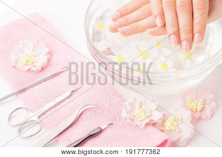 Beautiful woman hands with french manicure and instruments on pink towel
