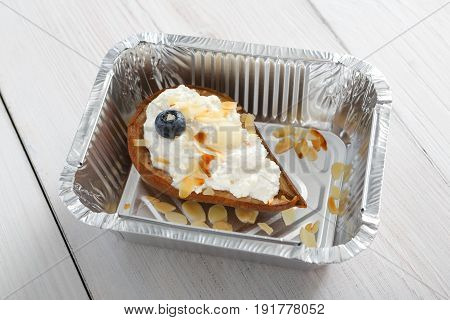 Restaurant food take away in foil box. Sweet breakfast - baked pea with mascarpone cream dessert, almond slices and bluberries.