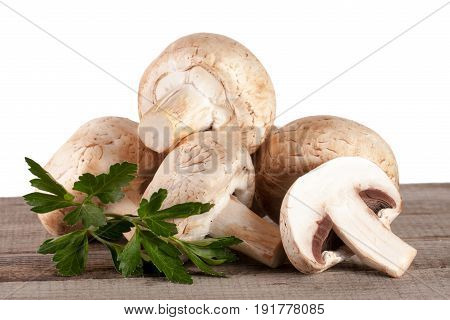 Champignon mushrooms on wooden table with white background.