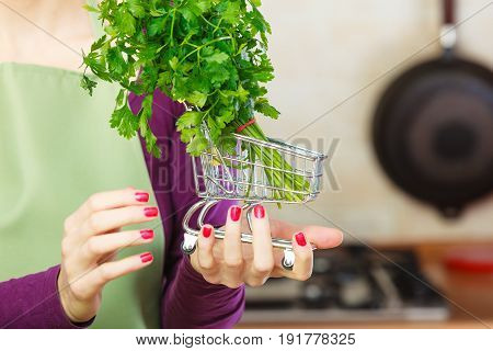 Buying healthy dieting food concept. Woman in kitchen having many green vegetables holding small shopping cart trolley with parsley inside.