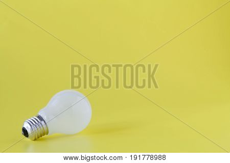 plain light bulb on plain bright yellow background