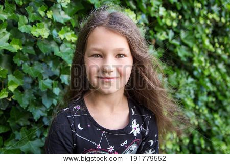 Portrait of little girl. Pre-teen child on the background of green leaves.