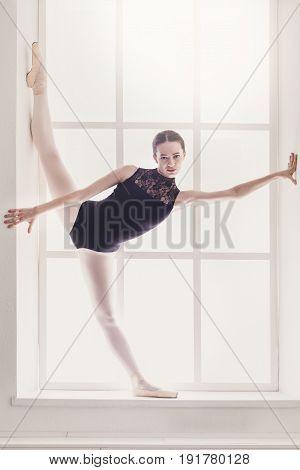 Ballerina. Classical Ballet dancer in standing split on window