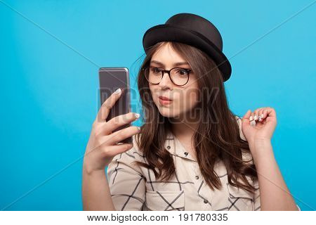 Young woman in hat and glasses holding smartphone and looking embarrassed.