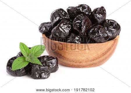 Dried plums or prunes with a mint leaf in wooden bowl isolated on white background.
