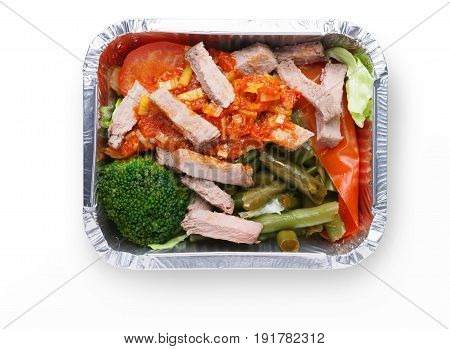 Healthy food background. Daily take away meals. Dietary restaurant food delivery. Steamed meat with vegetable salad and sauce in foil box isolated on white background, closeup