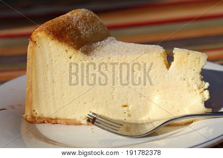 Slice Of Cheesecake On White Plate With Fork