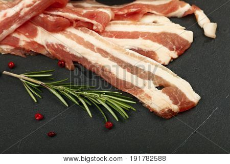 Raw Bacon Slices And Rosemary On Black Board